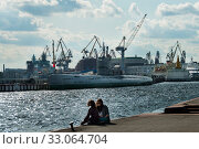 SAINT PETERSBURG, RUSSIA - september 12, 2019: two young girl sit in front of s-189 soviet submarine on Lieutenant Schmidt embankment on right of Neva river. Стоковое фото, фотограф Короленко Елена / Фотобанк Лори
