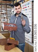 Купить «male seller sorting boxes with door handles in houseware shop», фото № 33065036, снято 5 апреля 2017 г. (c) Яков Филимонов / Фотобанк Лори