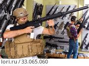Купить «Male customers try on ammunition with weapon», фото № 33065060, снято 4 июля 2017 г. (c) Яков Филимонов / Фотобанк Лори