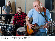 Купить «Modern male singer rehearsing with band», фото № 33067912, снято 26 октября 2018 г. (c) Яков Филимонов / Фотобанк Лори
