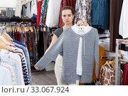 Купить «Woman choosing new clothes in shop», фото № 33067924, снято 10 октября 2018 г. (c) Яков Филимонов / Фотобанк Лори