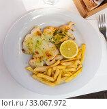 Купить «Fried sepia with green sauce, fries and lemon», фото № 33067972, снято 26 февраля 2020 г. (c) Яков Филимонов / Фотобанк Лори