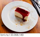 Купить «Slice of delicious classical cheesecake with fruity sauce served in cafeteria», фото № 33068140, снято 6 июля 2020 г. (c) Яков Филимонов / Фотобанк Лори