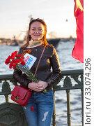 Купить «Portrait of young Russian woman with red carnations in hands, celebrating of the 70 aniversary of the Victory Day in World War II. St. Petersburg, Russia», фото № 33074296, снято 9 мая 2015 г. (c) Кекяляйнен Андрей / Фотобанк Лори