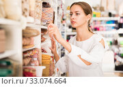 Купить «Seamstress looking for ribbons in haberdasher shop», фото № 33074664, снято 18 октября 2019 г. (c) Яков Филимонов / Фотобанк Лори