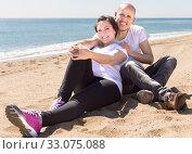 elderly man with a woman in white shirts sitting on sand on beach. Стоковое фото, фотограф Татьяна Яцевич / Фотобанк Лори