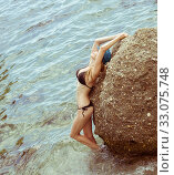 Купить «Beautiful slim young woman in a black bikini swimsuit resting on a rocky beach», фото № 33075748, снято 20 июля 2016 г. (c) katalinks / Фотобанк Лори
