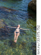 Beautiful slim young woman in a black bikini swimsuit resting on a rocky beach (2016 год). Стоковое фото, фотограф katalinks / Фотобанк Лори
