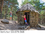 Купить «Little daughter, five years old girl, pointing with finger, next to her mother, both mountaineers, in ancient hut in forest of Canencia mountain (Madrid, Spain, Europe).», фото № 33079568, снято 19 августа 2018 г. (c) easy Fotostock / Фотобанк Лори