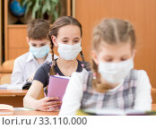 Schoolkids with medicine mask on faces against virus in classroom. Стоковое фото, фотограф Оксана Кузьмина / Фотобанк Лори