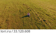 Купить «Low orbital flight around man on green grass with notebook pad at yellow rural field.», видеоролик № 33120608, снято 13 марта 2019 г. (c) Александр Маркин / Фотобанк Лори