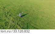 Купить «Low orbital flight around man on green grass with notebook pad at yellow rural field.», видеоролик № 33120832, снято 15 марта 2019 г. (c) Александр Маркин / Фотобанк Лори