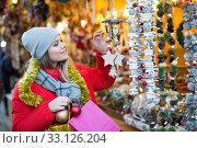 Купить «Young female near counter with xmas gifts on street market», фото № 33126204, снято 1 декабря 2018 г. (c) Яков Филимонов / Фотобанк Лори
