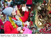 Купить «Happy girl chooses Christmas toys on the street market», фото № 33126224, снято 1 декабря 2018 г. (c) Яков Филимонов / Фотобанк Лори