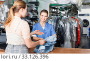 Купить «Young woman worker of laundry taking clothes for dry cleaning from female client», фото № 33126396, снято 9 мая 2018 г. (c) Яков Филимонов / Фотобанк Лори
