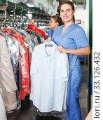 Worker of laundry demonstrating clean garment. Стоковое фото, фотограф Яков Филимонов / Фотобанк Лори