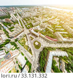 Купить «Aerial city view with crossroads and roads, houses, buildings, parks and parking lots. Sunny summer panoramic image», фото № 33131332, снято 29 марта 2020 г. (c) Александр Маркин / Фотобанк Лори