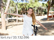 Купить «Positive teen girl standing near bicycle ready to go on park ride», фото № 33132096, снято 20 июля 2018 г. (c) Яков Филимонов / Фотобанк Лори