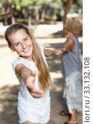 Teen girl girl pulling hand and keep grandmother on hand in green park. Стоковое фото, фотограф Яков Филимонов / Фотобанк Лори
