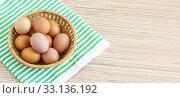 Свежие куриные яйца от домашней птицы в плетеной корзинке на зеленой салфетке. Свободное место для текста. Стоковое фото, фотограф Наталья Гармашева / Фотобанк Лори