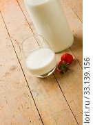 Купить «Photo of cup of milk with strawberry on wooden table», фото № 33139156, снято 19 февраля 2020 г. (c) easy Fotostock / Фотобанк Лори