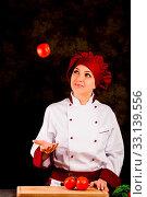 Купить «Photo of female chef juggling with tomato on dark rural background», фото № 33139556, снято 19 февраля 2020 г. (c) easy Fotostock / Фотобанк Лори