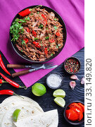 spicy slow-cooked pulled beef with chili pepper in a bowl, tortillas, lime wedges, salt on a black wooden table, horizontal view from above, flatlay. Стоковое фото, фотограф Oksana Zh / Фотобанк Лори