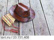 Купить «Multiple pipes pan flute and leather cowboy hat lying on square-edged flooring, copy space», фото № 33151408, снято 31 июля 2014 г. (c) Кекяляйнен Андрей / Фотобанк Лори