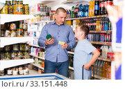 Купить «Young father and son making purchases together with shopping list», фото № 33151448, снято 4 июня 2018 г. (c) Яков Филимонов / Фотобанк Лори
