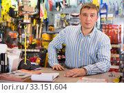 Купить «Glad seller man in store is trading tools», фото № 33151604, снято 22 октября 2019 г. (c) Яков Филимонов / Фотобанк Лори
