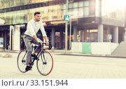 Купить «man with headphones riding bicycle on city street», фото № 33151944, снято 21 августа 2016 г. (c) Syda Productions / Фотобанк Лори
