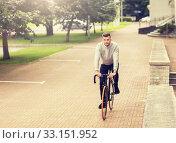Купить «young man riding bicycle on city street», фото № 33151952, снято 21 августа 2016 г. (c) Syda Productions / Фотобанк Лори
