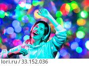 Купить «woman in headphones dancing over night lights», фото № 33152036, снято 30 сентября 2019 г. (c) Syda Productions / Фотобанк Лори