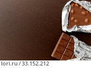 Купить «milk chocolate bar with nuts in foil wrapper», фото № 33152212, снято 1 февраля 2019 г. (c) Syda Productions / Фотобанк Лори
