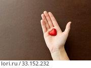 Купить «hand with red heart shaped chocolate candy», фото № 33152232, снято 1 февраля 2019 г. (c) Syda Productions / Фотобанк Лори