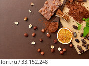 Купить «chocolate with hazelnuts, cocoa beans and powder», фото № 33152248, снято 1 февраля 2019 г. (c) Syda Productions / Фотобанк Лори