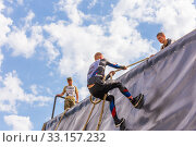 Купить «Russia, Samara, June 2019: a young sports man with the help of a rope overcomes the most difficult obstacles in the race of Everest heroes.», фото № 33157232, снято 8 июня 2019 г. (c) Акиньшин Владимир / Фотобанк Лори