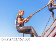 Купить «Russia, Samara, June 2019: Young beautiful girl overcomes the most difficult obstacle in the race of heroes of Everest with the help of a rope», фото № 33157360, снято 8 июня 2019 г. (c) Акиньшин Владимир / Фотобанк Лори