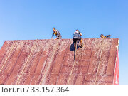 Купить «Russia, Samara, June 2019: a young sports man with the help of a rope overcomes the most difficult obstacles in the race of Everest heroes.», фото № 33157364, снято 8 июня 2019 г. (c) Акиньшин Владимир / Фотобанк Лори