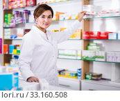 Купить «Cheerful pharmacist offering reliable medicine», фото № 33160508, снято 31 января 2017 г. (c) Яков Филимонов / Фотобанк Лори