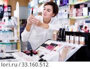 Купить «Customer browsing rows of cosmetic products», фото № 33160512, снято 31 января 2017 г. (c) Яков Филимонов / Фотобанк Лори