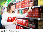 Купить «Woman choosing cold beer in supermarket», фото № 33160516, снято 23 ноября 2016 г. (c) Яков Филимонов / Фотобанк Лори
