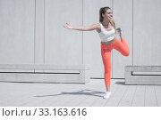 Happy Sporty Pretty Girl Doing an Outdoor Exercise. Стоковое фото, фотограф Piotr Stryjewski / PantherMedia / Фотобанк Лори