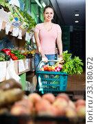 Купить «Portrait of young satisfied female purchaser holding shopping basket with fruits and vegetables», фото № 33180672, снято 14 октября 2017 г. (c) Яков Филимонов / Фотобанк Лори