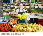 Купить «Portrait of smiling saleswoman with cluster of yellow bananas in store», фото № 33180676, снято 14 октября 2017 г. (c) Яков Филимонов / Фотобанк Лори