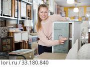 Купить «Portrait of smiling female choosing bedside table», фото № 33180840, снято 15 ноября 2017 г. (c) Яков Филимонов / Фотобанк Лори