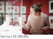 Купить «Young woman visitor using phone in museum», фото № 33180852, снято 18 ноября 2017 г. (c) Яков Филимонов / Фотобанк Лори