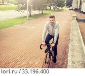 Купить «young man riding bicycle on city street», фото № 33196400, снято 21 августа 2016 г. (c) Syda Productions / Фотобанк Лори