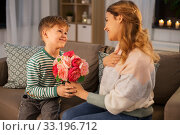 Купить «smiling little son gives flowers to mother at home», фото № 33196712, снято 14 декабря 2019 г. (c) Syda Productions / Фотобанк Лори