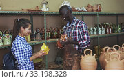 Купить «Afro-american seller offers woman traditional handmade african pottery», видеоролик № 33198328, снято 28 мая 2020 г. (c) Яков Филимонов / Фотобанк Лори